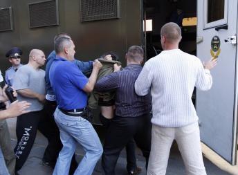 Погрузка в автозак одного из участников акции Революция через социальные сети