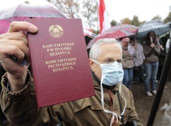 Участник Народного схода оппозиции в Минске с Конституцией Республики Беларусь 8 октября 2011